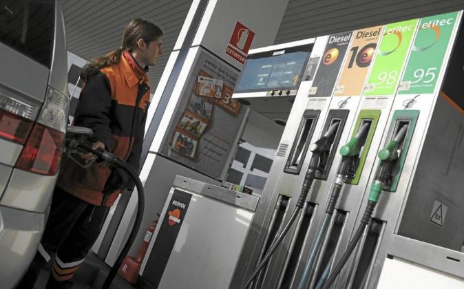 Trabajador repostando un coche en una  gasolinera de Madrid.