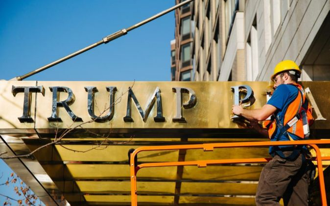 """Un obrero retira el nombre de """"Trump Place""""."""