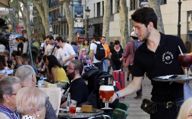 Un camarero trabajando en una terraza en Barcelona.