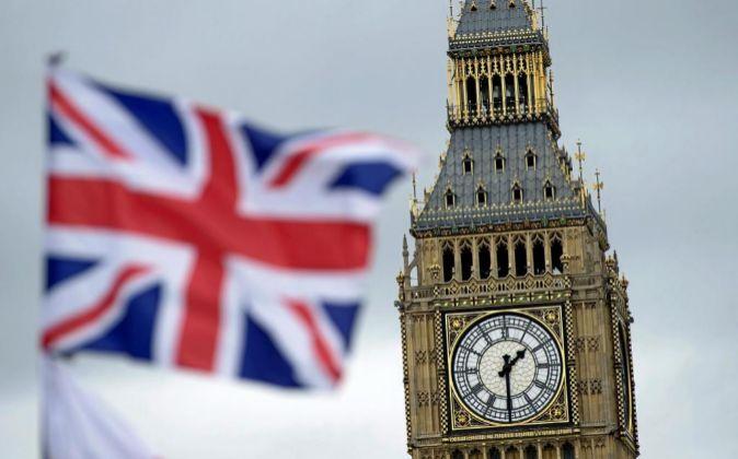Una bandera británica ondea junto al Big Ben de Londres, Reino Unido.