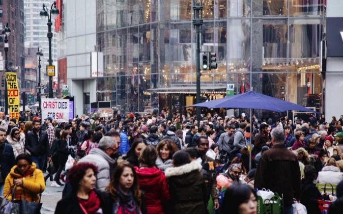 Cientos de personas caminan tras sus compras del 'Black...