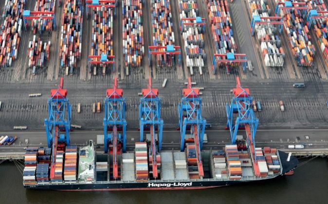 Varias grúas descargan contenedores de un buque carguero en el puerto...