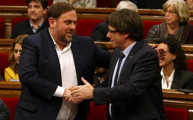El presidente de la Generalitat, Carles Puigdemont (d), da la mano al...