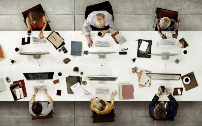 Varias personas trabajando en una mesa de oficina.