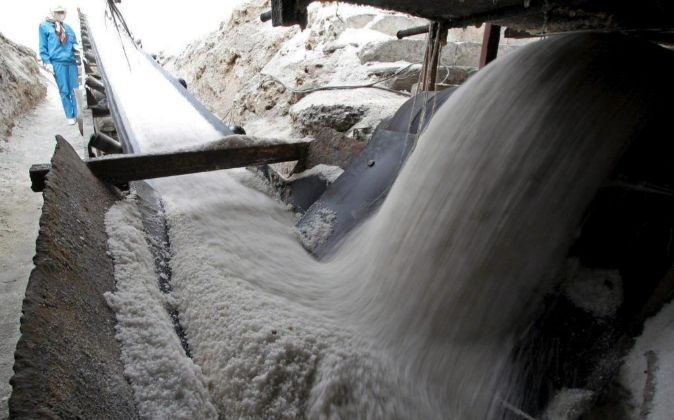 Un trabajador supervisa la caída de sal sobre una cinta...