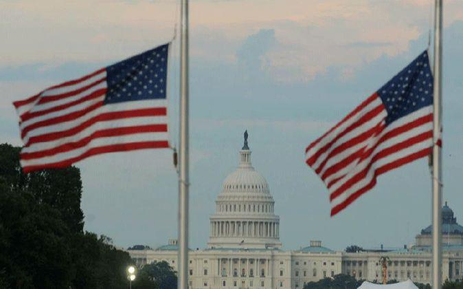 Imagen de banderas de EEUU con la Casa Blanca de fondo