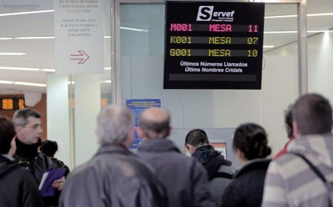 Un grupo de personas espera su turno en una oficina del servicio...