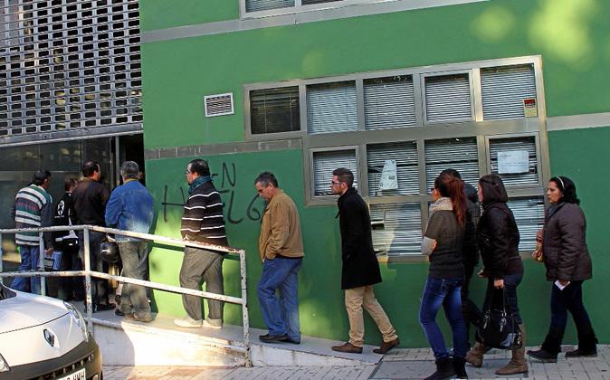 Un grupo de personas hace cola a las puertas de una oficina del SAS en...