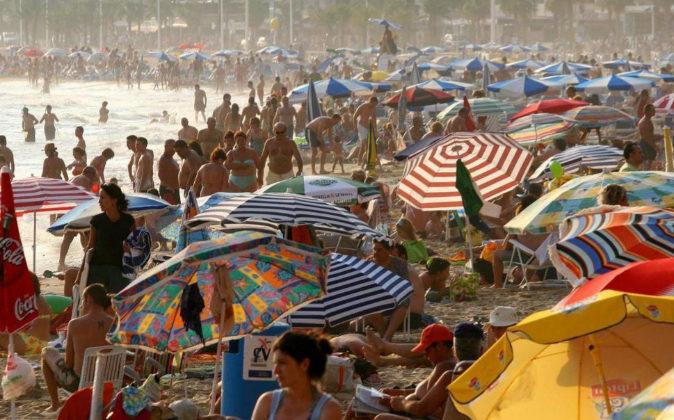 Multitud de turistas abarrotan la playa de Levante, en la ciudad...