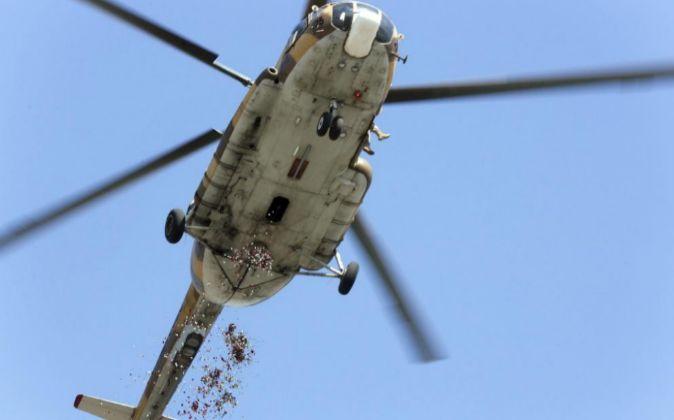 Un helicóptero lanza pétalos de flores durante el funeral por los...