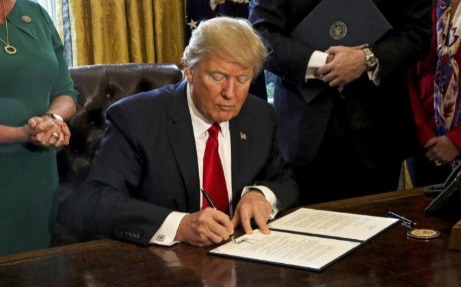 Donald Trump firma una orden ejecutiva en el Despacho Oval de la Casa...