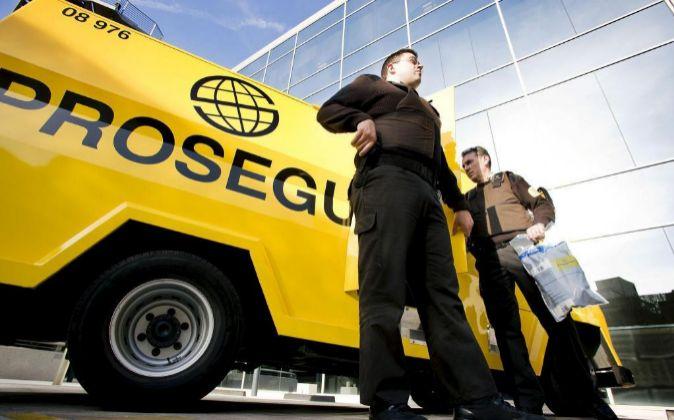 Empleados de Prosegur junto a uno de sus furgones.