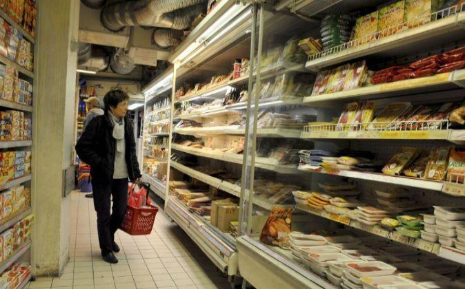 Una clienta observa las estanterías de un supermercado en París,...