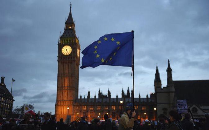 Varias personas manifiestan con pancartas y ondean la bandera de la...