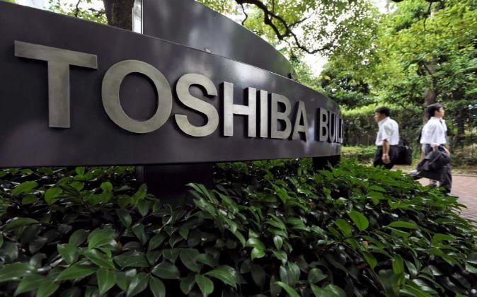 Dos hombres caminan frente a la sede de la empresa japonesa de...
