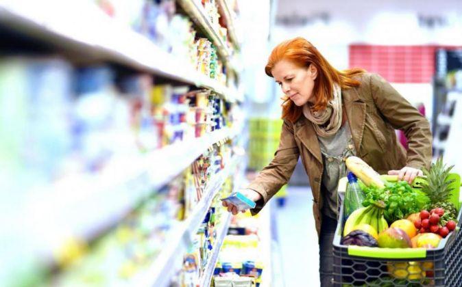 Una mujer mira el precio de los alimentos en el supermercado.