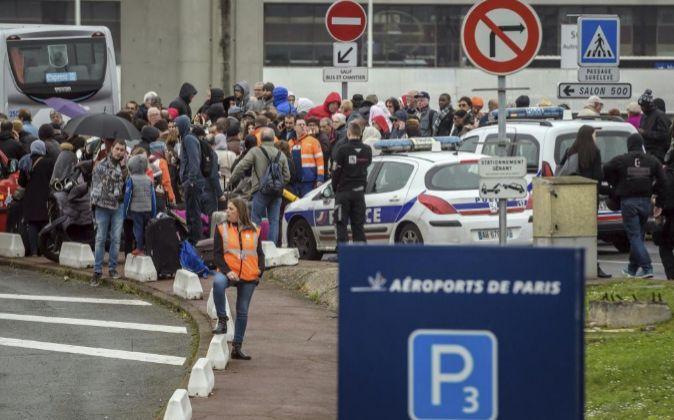 Varios pasajeros, evacuados de Orly, congregados en los alrededores...