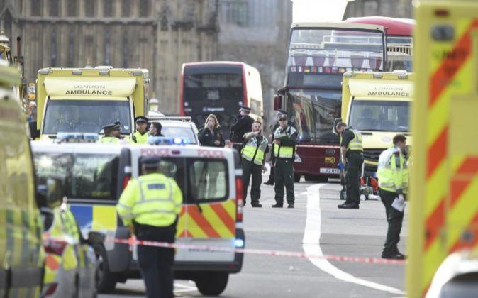 Agentes de policía británicos permanecen en guardia tras un tiroteo...
