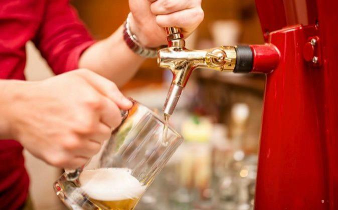 Un camarero tira cerveza en un bar.