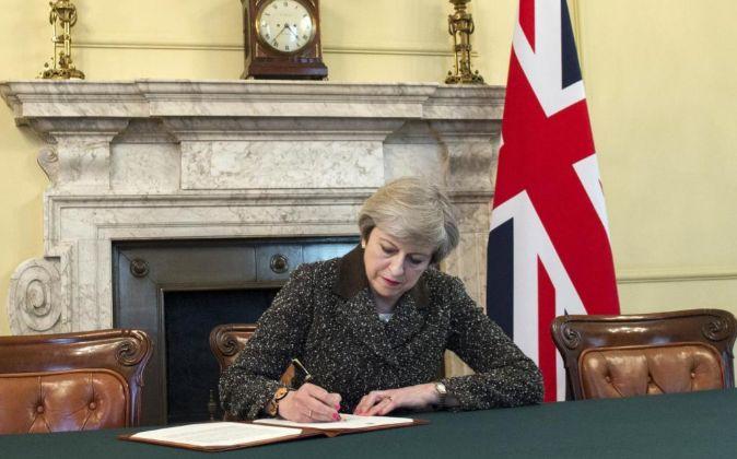 La primera ministra británica, Theresa May, firma la carta con la que...