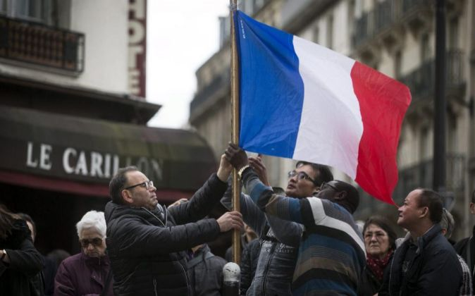 Tres personas colocan una bandera francesa ante el bar le Carillon de...