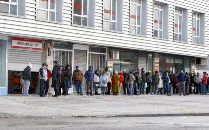 Varias personas forman una larga cola ante una oficina del INEM, a...