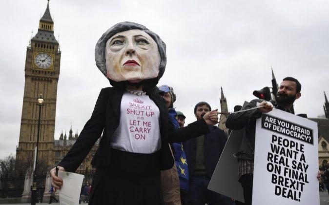 Una manifestante disfrazada de la primera ministra británica, Theresa...