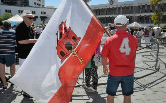 Un hombre sostiene la bandera de Gibraltar