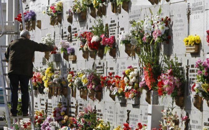Un hombre coloca unas flores en la tumba de un familiar en el...