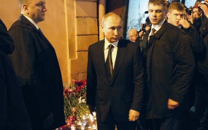 El presidente ruso, Vladimir Putin (c), coloca una ofrenda floral...