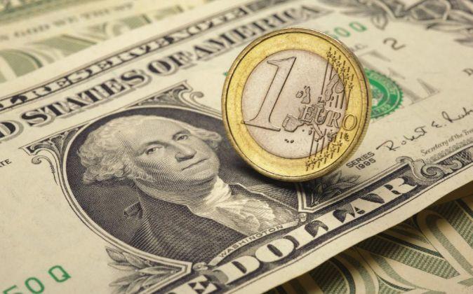 Imagen de una moneda de euro encima de un billete de dólar