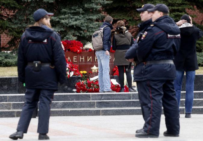 Policías rusos patrullan cerca de los ramos de flores dejados en...