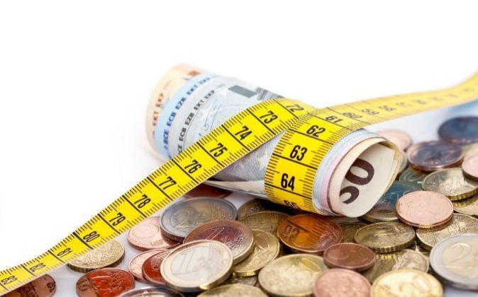 Billetes del euro rodeados por una cinta métrica.