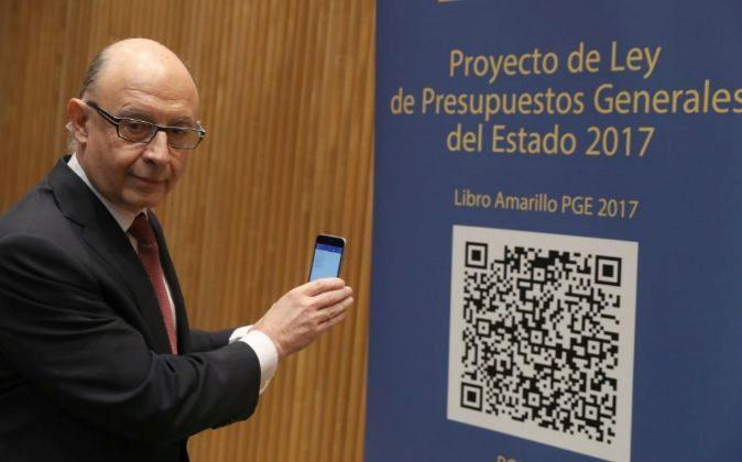 El ministro de Hacienda, Cristóbal Montoro, escanea con el móvl el...