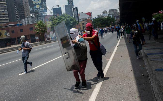Un grupo de manifestantes se enfrenta con la policía durante una de...