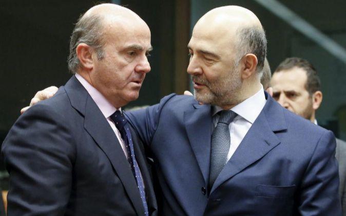 El ministro español de Economía, Luis de Guindos (i) conversa con el...