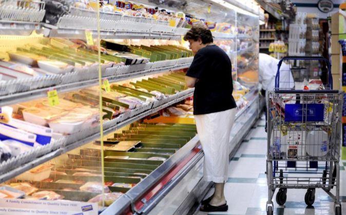 Una mujer selecciona productos en un supermercado de Brooklyn, Nueva...