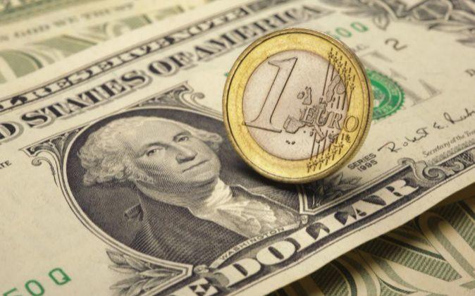 Imagen de una moneda de un euro sobre un billete de dólar