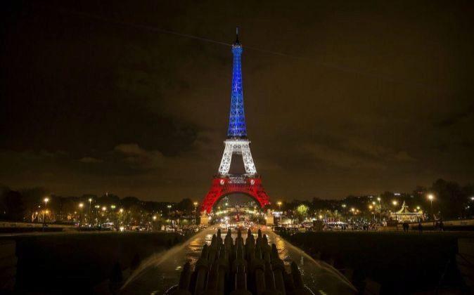 Vista de la torre Eiffel iluminada con los colores de la bandera...