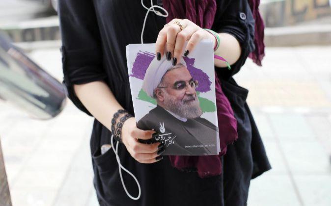 Una joven muestra un cartel electoral del presidente y candidato a las...