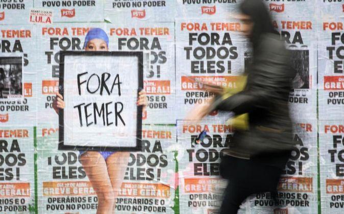 Una persona pasa frente a un muro lleno de carteles en contra del...