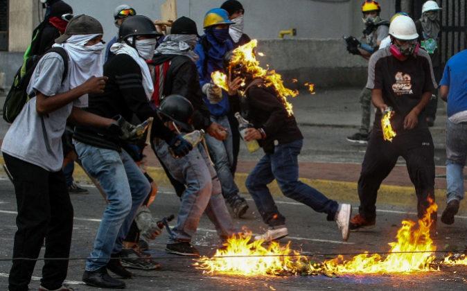 Opositores se enfrentan a la Guardia Nacional Bolivariana ayer lunes,...