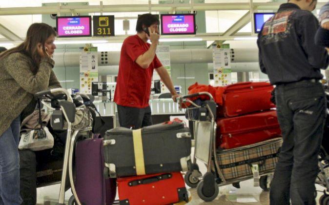 Varias personas esperan en el aeropuerto de El Prat, en Barcelona.