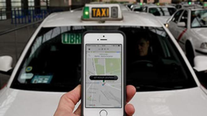 Una persona porta un móvil frente a un taxi.