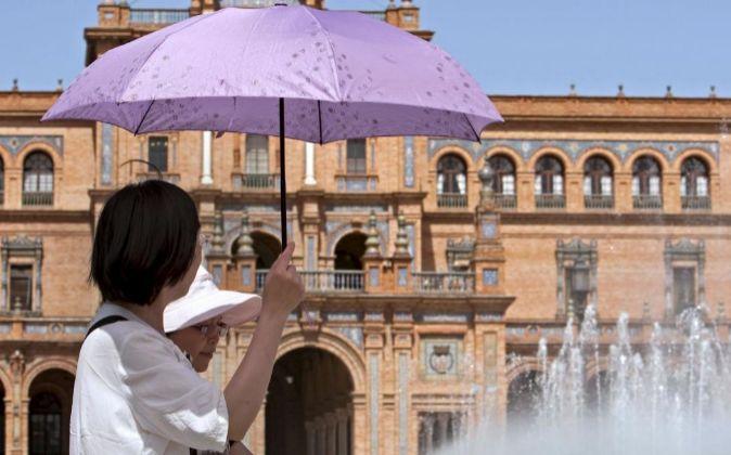 Turistas extranjeros recorren la plaza de España de Sevilla.