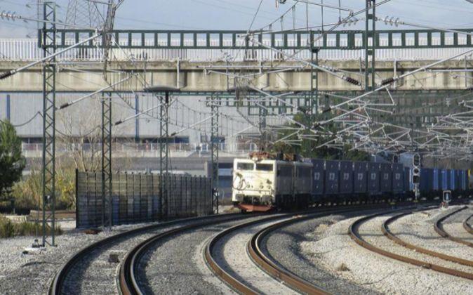 Un tren de mercancías de Renfe circula por el tercer hilo en el...