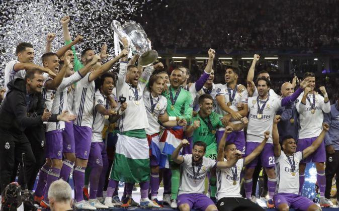 Los jugadores del Real Madrid levantan el trofeo que les acredita como...