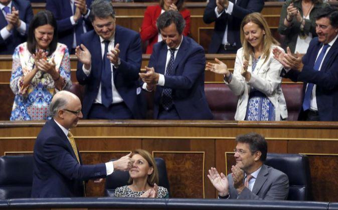 El ministro de Hacienda, Cristóbal Montoro (i), recibe el aplauso de...