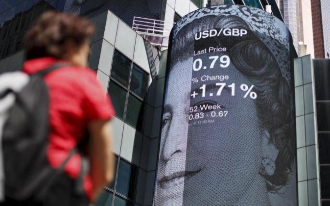Una cartelera con el cambio de divisas muestra la caída de la libra...