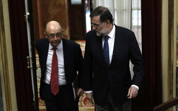 El presidente del Gobierno, Mariano Rajoy (d), y el ministro de...